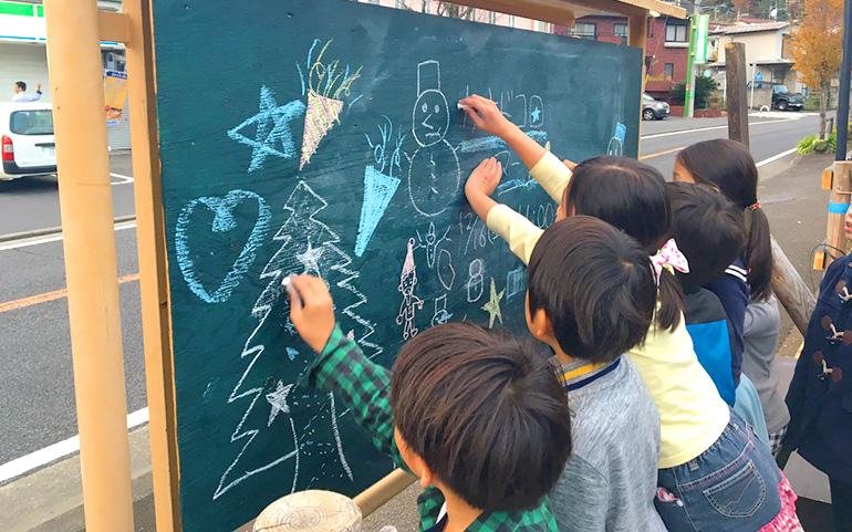黒板にマーケットの宣伝を描く子どもたち