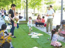 「みち」に出現した人工芝の上でフラフープをしたり、けん玉をしたりして遊ぶ参加者たち