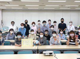 感謝状を手に記念撮影をするプロジェクトメンバーと多田貴栄麻生区長
