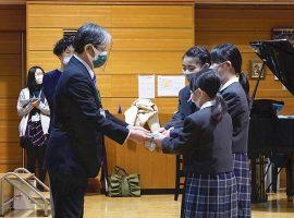 緑の郷の理事長と施設長にDVDとパンフレットを手渡す子どもたち。