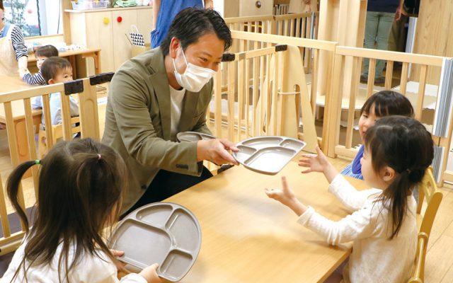 園児たちに岡上産バイオマス食器を手渡す(株)カルナエスト代表の山田貢さん。